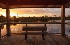 在一条偏僻,平静的木板走道的日落长木凳沿一ma 免版税库存图片