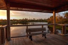 在一条偏僻,平静的木板走道的日落长木凳沿一ma 库存图片