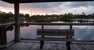 在一条偏僻,平静的木板走道的日落长木凳沿一ma 免版税图库摄影