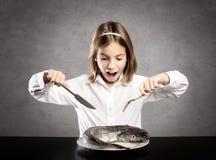在一条全部的生鱼前面的小饥饿的女孩 免版税库存照片