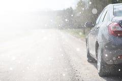 在一条农村路的一辆汽车在第一秋天雪 第一个冬天 库存图片