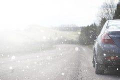 在一条农村路的一辆汽车在第一秋天雪 第一个冬天 免版税库存照片