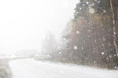 在一条农村路的一辆汽车在第一秋天雪 第一个冬天 图库摄影