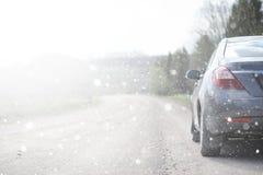 在一条农村路的一辆汽车在第一秋天雪 第一个冬天 库存照片