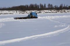 在一条冬天路的卡车沿河 免版税库存照片