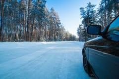 在一条冬天路的汽车在森林里 免版税库存照片