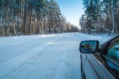 在一条冬天路的汽车在森林里 库存图片