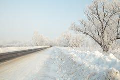 在一条冬天路的汽车在远处离开的森林 免版税库存图片