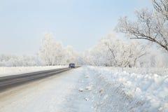 在一条冬天路的汽车在远处离开的森林 库存图片