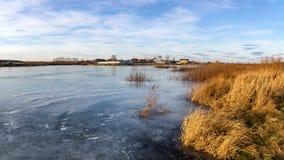 在一条冻河的秋天风景有在俄罗斯,乌拉尔的银行的树的 库存照片
