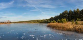 在一条冻河的秋天风景有在俄罗斯,乌拉尔的银行的树的 免版税图库摄影