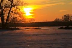 在一条冻河Dnieper的日落在冬天 免版税图库摄影
