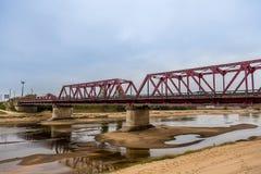 在一条几乎干燥河的金属桥梁在多云天空下 库存图片