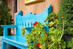 在一条古色古香的长凳前面的红色花 库存图片