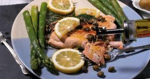 在一条可口烤有机三文鱼的倾吐的橄榄油 免版税库存图片