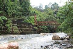 在一条圆鼓,冲的河的一座红色桥梁在Batatal小山的一有薄雾的天  免版税库存照片
