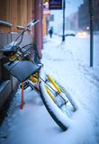 在一条城市街道上的一辆黄色自行车在冬天 库存图片