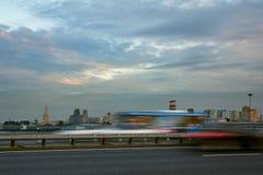 在一条城市街道上的交通在日落 免版税库存照片
