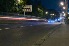 在一条城市街道上的交通在晚上 库存图片
