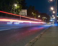在一条城市街道上的交通在晚上 免版税库存照片