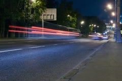 在一条城市街道上的交通在晚上 免版税图库摄影