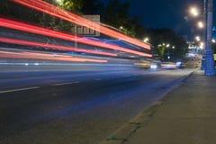 在一条城市街道上的交通在晚上 图库摄影