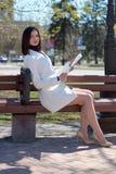 在一条城市街道上的典雅的年轻女人有一张报纸的在她的手上 库存照片