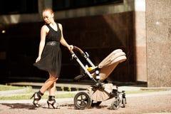 在一条城市街道上的时髦现代母亲有摇篮车的。年轻母亲 免版税库存图片
