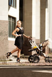 在一条城市街道上的时髦现代母亲有摇篮车的。年轻母亲 库存照片