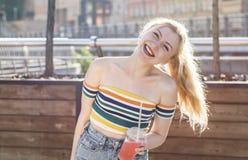 在一条城市街道上的美丽的年轻人微笑女孩在一个晴天喝与冰的刷新的水果鸡尾酒在一条短裙 库存图片