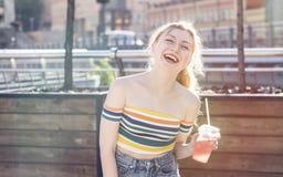 在一条城市街道上的美丽的年轻人微笑女孩在一个晴天喝与冰的刷新的水果鸡尾酒在一条短裙 免版税库存图片