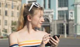 在一条城市街道上的美丽的年轻白肤金发的女孩在与寻找某事在地图的智能手机的一个晴天 免版税图库摄影