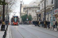 在一条城市街道在一多云天,伊斯坦布尔上的一辆现代电车 免版税库存照片