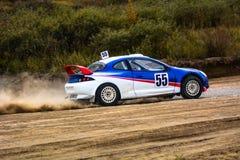 在一条多灰尘的路的赛车 免版税库存图片