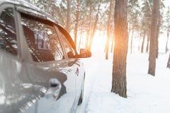 在一条多雪的冬天森林公路的一辆银色汽车 库存照片