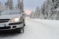 在一条多雪的山路的一辆汽车 免版税库存图片
