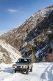 在一条多雪的山路的SUV 免版税库存照片