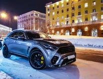 在一条多雪的街道上的凉快的汽车在晚上 免版税库存照片