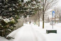 在一条多雪的街道上的步行者 库存照片