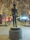 在一条多雪的街道上的雕象有彩色小灯的 库存图片