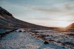 在一条多雪的道路的日落在冰岛 免版税库存图片