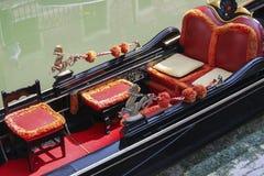 在一条威尼斯式运河的红色和黑长平底船 库存照片