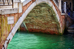 在一条威尼斯式运河的被成拱形的桥梁 免版税库存照片