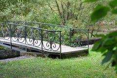 在一条安静的小河的小精美木被成拱形的桥梁深深在老,厚实的假日公园 免版税库存图片
