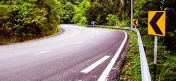 在一条安静的森林公路的一个弯 库存图片