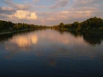 在一条宽河的日落:河的镇静水流动在与森林的岸之间,桃红色云彩反射表面o上 库存图片