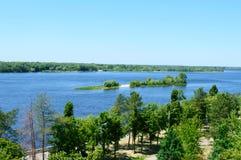 在一条宽河的美好的风景,有一个小海岛的,绿色银行,有鸟` s眼睛视图 晴朗日的夏天 库存照片