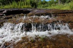在一条小小河的清楚的流动的水与绿色植被在背景中 免版税库存照片
