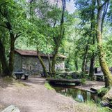 在一条小河旁边的老石农村房子有一个木桥的 库存照片