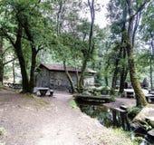在一条小河旁边的老石农村房子有一个木桥的 库存图片